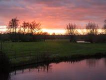 Rode zon het plaatsen hemel de dramatische herfst over lege open groene countr Royalty-vrije Stock Afbeelding