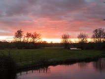 Rode zon het plaatsen hemel de dramatische herfst over lege open groene countr Stock Foto's
