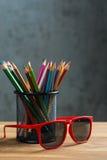 Rode zonglazen met bos van kleurenpotloden in een tribune Stock Foto