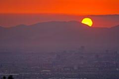 Rode zonsondergang achter bergen over een stad Stock Afbeelding