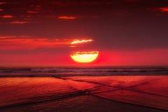 Rode zonsondergang met grote zon over overzees royalty-vrije stock foto's