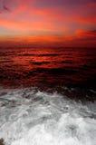Rode zonsondergang met het breken van water. Royalty-vrije Stock Fotografie