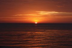 Rode zonsondergang over de oceaan stock afbeelding