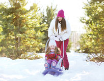 Rodelndes Kind der Mutter im sonnigen Winter Stockbilder