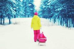 Rodelndes Kind der Mutter im Winter Stockfotografie