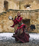 Cave-Woman Dancing. Rodemack,France- December 09, 2012: An actress disguised as a cave-woman is dancing outside,near the fortress walls, while sleeting, during a stock image
