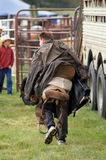 Rodeo. Young Rodeo Cowboy carrying his saddle and other gear in preparation for Rodeo competitions stock photography