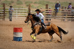 Rodeo Barrel Racing. A cowgirl rounds a barrel during the barrel racing competition at the Galiesto, New Mexico rodeo on July 21, 2013 royalty free stock photo