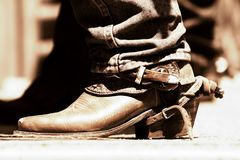 Rodeo Boot & Spur (Copper Tone). A rodeo cowboy's boot and spur behind the scenes of a daytime rodeo competition (shallow focus, copper tone stock images