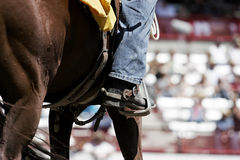 Rodeo Boot, Spur, & Horse. Close-up of a cowboy's boot and spur while he sits astride his horse at a large rodeo (shallow focus royalty free stock photography