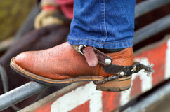 Rodeo Boots and Spurs. Detail close up of Rodeo Cowboy's leather boot and spurs, standing on fence railing royalty free stock image