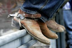 Rodeo Boots & Spurs. Rodeo cowboys' experienced boots & spurs on an iron rail (shallow focus royalty free stock photography