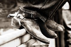 Rodeo Boots & Spurs (BW). Rodeo cowboys' experienced boots & spurs on an iron rail (shallow focus, high contrast black & white royalty free stock photos