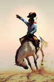 Rodeo. Cowboy on a wild  white horse bucking over the sand Stock Image