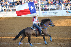 Rodeo Queen with Texas Flag. Rodeo Queen riding out with the Texas flag during opening ceremonies at a small town rodeo stock photo