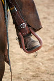 Rodeo rider's foot in stirrup. A rider's boot and leathers in a stirrup. Shot at a local rodeo meet Royalty Free Stock Photos
