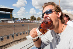 Rodeo Snack. A young man taking a big bite of a deep fried turkey leg as a snack at a rodeo in Northern Idaho Stock Photography