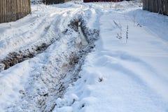 Rodera con los charcos Rastros de neumáticos del tractor en nieve Imagenes de archivo
