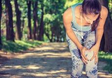 Rodilla conmovedora en dolor, mujer del corredor del atleta de sexo femenino de la aptitud que corre en parque fotografía de archivo libre de regalías