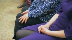 Rodilla femenina de la mujer que se sienta en asiento Mujer que toca la rodilla que se sienta en silla almacen de metraje de vídeo
