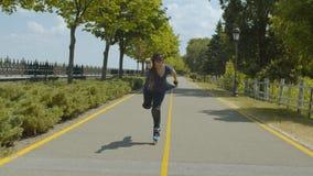 Rodillo alegre de la mujer que se divierte que patina en parque metrajes