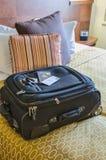 Rodillo a bordo del bolso en una cama del hotel Imagenes de archivo