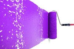 Rodillo con la pintura púrpura en la pared blanca Foto de archivo
