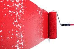 Rodillo con la pintura roja en la pared blanca Foto de archivo