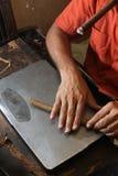 Rodillo cubano de los cigarros que hace su trabajo mientras que fuma Imagen de archivo