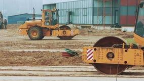 Rodillo de camino amarillo que trabaja en sitio de la construcción de carreteras Preparación de área constructiva almacen de metraje de vídeo