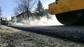 Rodillo de camino en el asfalto caliente
