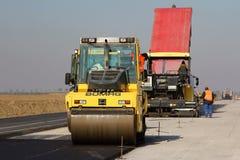 Rodillo de camino que nivela el pavimento fresco del asfalto en una pista como parte del plan de expansión del aeropuerto interna Foto de archivo