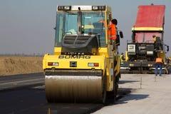 Rodillo de camino que nivela el pavimento fresco del asfalto en una pista como parte del plan de expansión del aeropuerto interna Imágenes de archivo libres de regalías