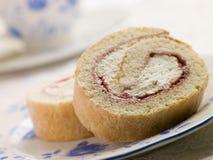 Rodillo de la esponja de la crema y de la fresa con té imágenes de archivo libres de regalías
