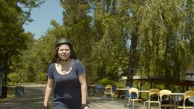 Rodillo de la mujer joven durante paseo de la velocidad en parque verde almacen de metraje de vídeo