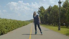 Rodillo de la mujer joven que goza de freeride en parque verde almacen de video