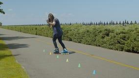 Rodillo de la mujer que entrena a aire libre patinador en línea almacen de video