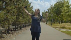 Rodillo de la mujer que fluye el vídeo en línea durante paseo almacen de video