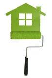 Rodillo de pintura y casa verde Fotos de archivo libres de regalías