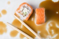 Rodillo del sushi en palillos en salsa de soja Fotografía de archivo libre de regalías