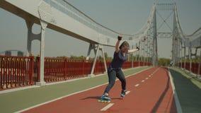 Rodillo femenino alegre que frena durante rollerblading almacen de video
