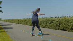 Rodillo femenino en línea que patina al revés en parque metrajes