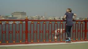 Rodillo femenino que disfruta de paisaje urbano durante el patinaje almacen de metraje de vídeo