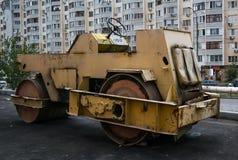 Rodillo oxidado para poner el asfalto Ciudad, calle, buil de varios pisos foto de archivo
