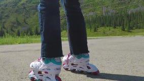 Rodillo-patinador Primer tirado de piernas femeninas en los patines en línea que se mueven en la trayectoria que camina C?mara le metrajes
