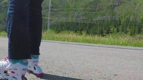 Rodillo-patinador Primer tirado de piernas femeninas en los patines en línea que se mueven en la trayectoria que camina C?mara le almacen de video