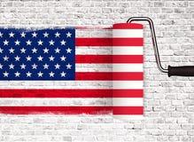 Rodillo a pintar en la pared de ladrillo blanca con la bandera americana de los E.E.U.U., pared con la pintura del goteo Fotos de archivo