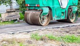 Rodillo que rueda el nuevo asfalto en el pavimento Fotos de archivo