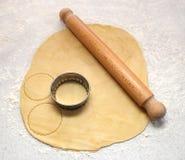 Rodillo y cortador en los pasteles frescos, cortando círculos Imagenes de archivo