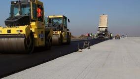Rodillos de camino que nivelan el pavimento fresco del asfalto almacen de video